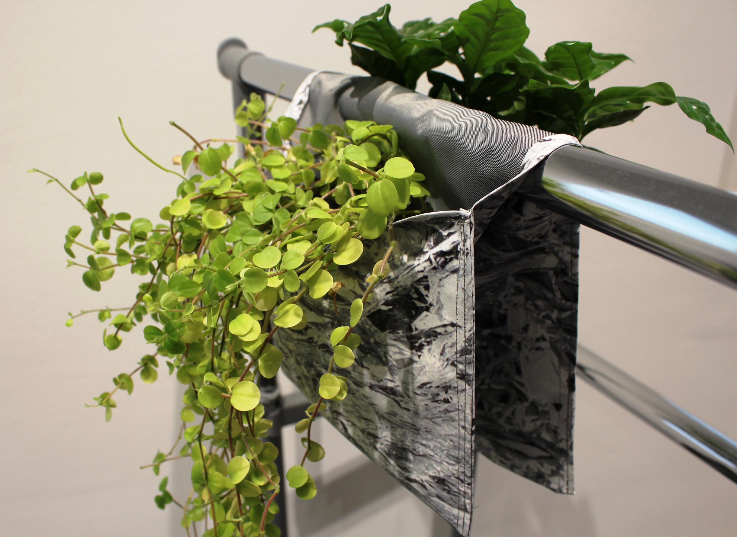 Eine Pflanztasche mit zwei Grünpflanzen hängt über einem Geländer